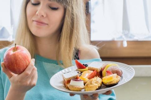 Eine Frau hält einen Apfel und ein Teller mit Süßem und entschließt sich für eine Ernährungsumstellung