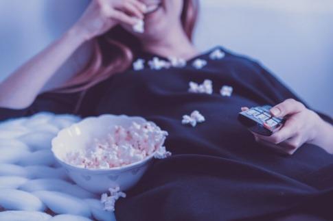 Eine Frau isst Popcorn während sie Fernsehen schaut