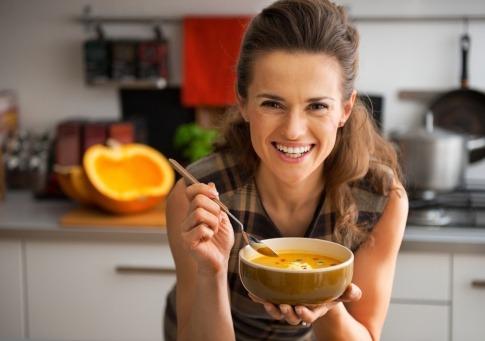 Frau isst Kürbiscremesuppe für Haarwachstum
