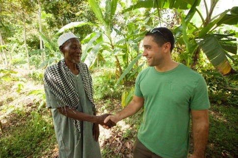 Ein Mitarbeiter von FAIRTRADE schüttelt einem FAIRTRADE-Produzenten die Hand