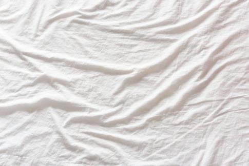 Weißes Leintuch wirft Falten.