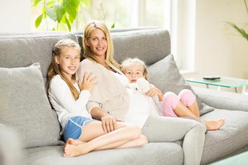 Eine Frau sitzt mit den Kindern auf einer Couch und genießt familiengerechtes Wohnen