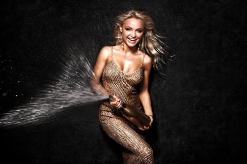 Eine blonde Frau mit langen Haaren und einem glamourösen Paillettenkleid hält eine Sektflasche in der Hand