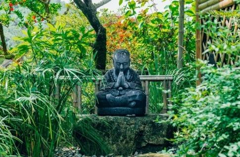 In einem Feng Shui Garten befindet sich eine Buddhastatue aus Stein