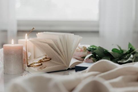 Ein aufgeschlagenes Buch, Ringe und Kerzen