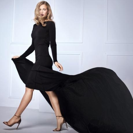 Eine Frau mit blonden langen Haaren trägt ein schwarzes Abendkleid mit Schleppe und High-Heels