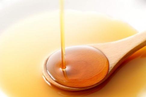 Öl tropft auf einen Holzlöffel