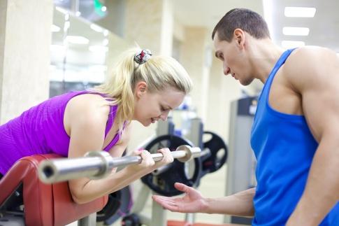 Ein Fitnesstrainer hilft einer Frau bei einer Hantel