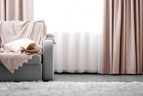 In einem Wohnzimmer liegt ein weißer flauschiger Teppich