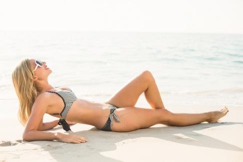 Eine Frau im Bikini liegt am Strand