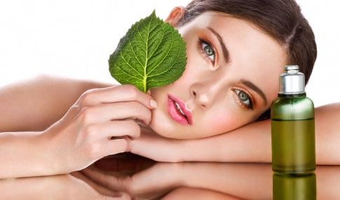 Eine Frau mit einem grünen Blatt vor dem Gesicht