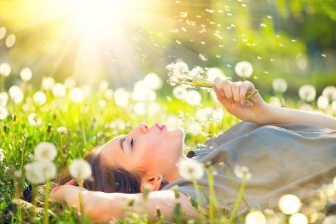 Eine Frau liegt auf einer Blumenwiese