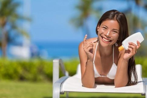 Eine Frau gibt Sonnenschutz auf ihr Gesicht