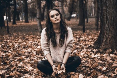Eine Frau mit emotionalem Schmerz sitzt am Boden