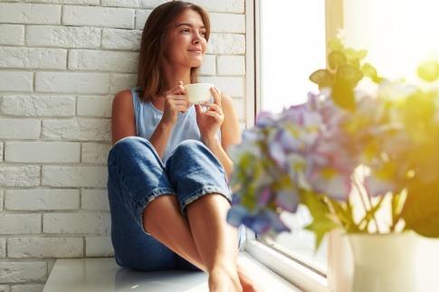 Eine Frau sitzt entspannt mit einer Tasse Kaffee am Fensterbrett und betrachtet die Natur