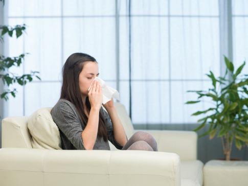 Eine Frau sitzt mit Erkältung auf einer Couch