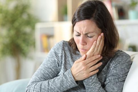 Eine Frau hat Schmerzen wegen einer Erkrankung im Mund