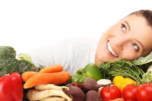 Eine Frau lehnt glücklich zwischen Obst, da sie faltenfrei durch Ernährung ist