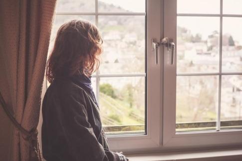Eine Frau sieht aus dem Fenster