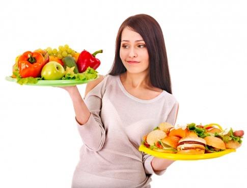 Eine Frau hält ein Teller gesunde Ernährung und ein Teller Burger in der Hand