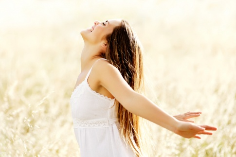 Eine Frau steht in einem Getreidefeld und sieht glücklich aus