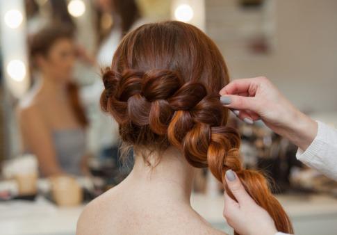 Eine dunkelhaarige Frau flechtet ihre Haare zu einem Zopf