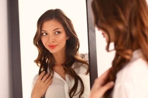 Eine Frau steht vor dem Spiegel und betrachtet ihre Haare