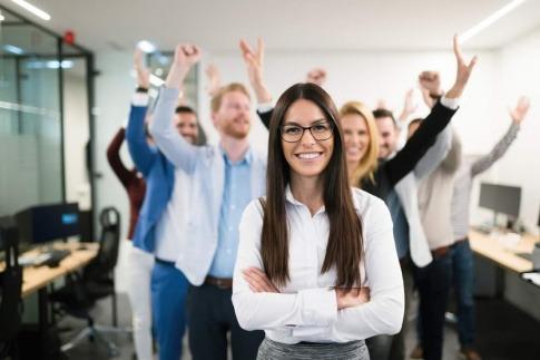Hinter einer Frau in der Führungsrolle steht ein jubelndes Team