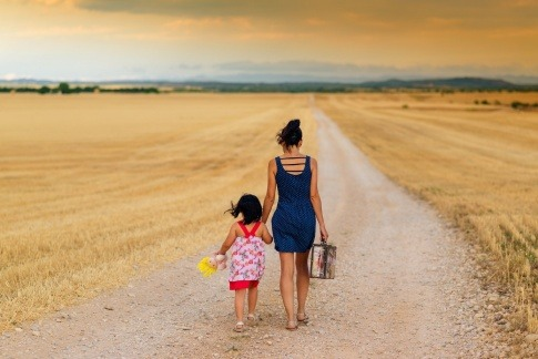 Eine Frau nimmt bei einer Reise ein Kind an der Hand