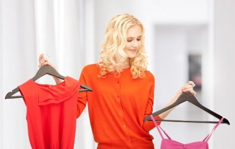 Eine Frau hält zwei Kleiderhaken mit Kleidung