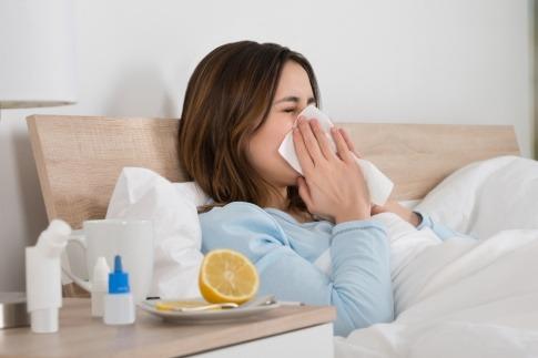Eine Frau liegt krank im Bett mit Taschentüchern