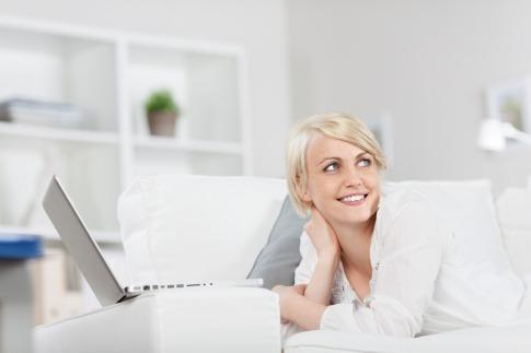 Eine Frau liegt mit einem Laptop auf einer Couch