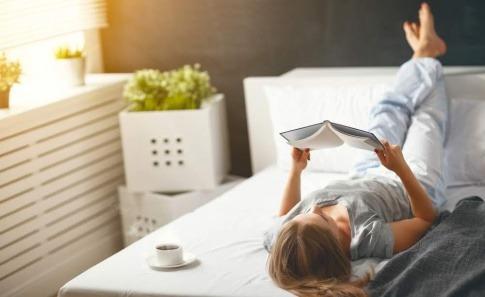 Eine Frau liegt im Bett und liest ein Buch