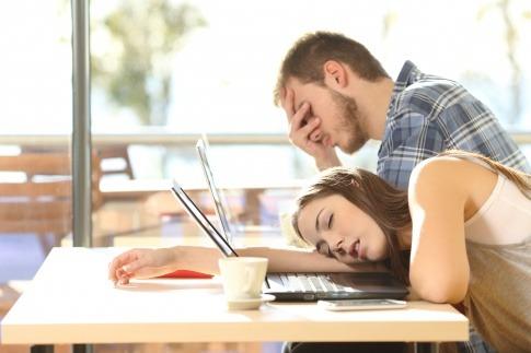 Eine Frau und ein Mann sind müde vom Arbeiten am Laptop