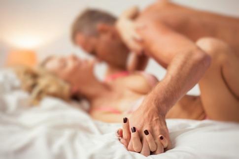 Ein älterer Mann und eine Frau liegen im Bett