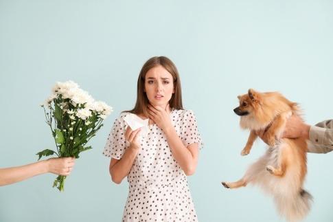 Einer Frau mit Allergie werden ein Blumenstrauß und ein Hund gereicht