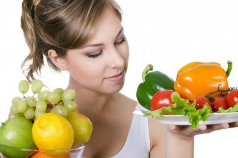 Eine Frau hält in der einen Hand einen Obstteller und in der anderen Hand einen Gemüseteller