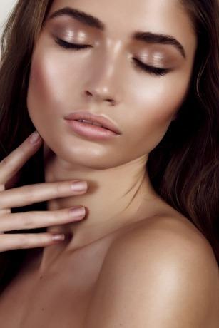 Eine Frau trägt ein Make-up mit vielen strahlenden Highlights