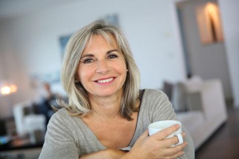 Eine Frau im mittleren Alter lächelt in die Kamera. Sie hält eine weiße Tasse in der Hand. Ihre Haare sind ergraut aber dennoch macht sie einen sehr glücklichen Eindruck.