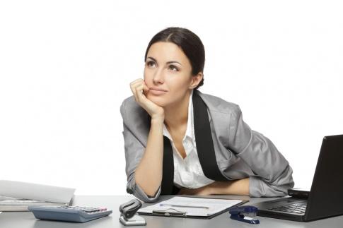 Eine Frau sitzt beim Laptop und sieht nachdenklich drein