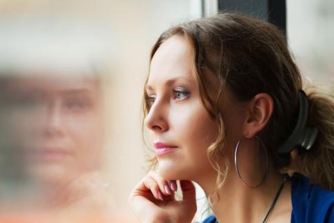 Eine Frau sieht nachdenklich aus dem Fenster raus
