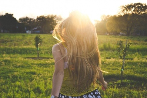 Eine Frau mit langen blonden Haaren befindet sich in der Natur