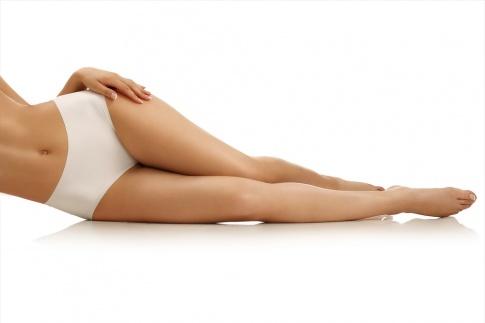 Eine Frau ohne Cellulite liegt in Unterwäsche