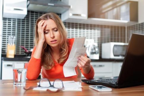 Eine Frau sitzt beim Schreibtisch und hält frustriert und verzweifelt Rechnungen