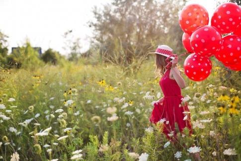 Eine Frau trägt rote Ballons