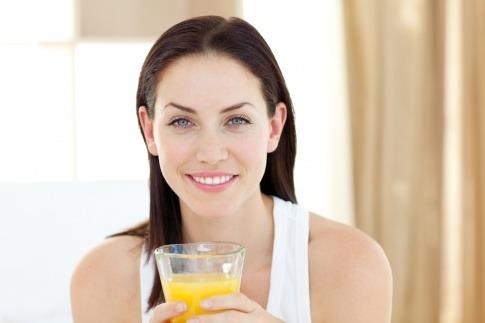 Eine Frau will fasten im Alltag und hält ein Glas Saft