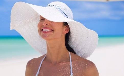 Eine Frau mit Sonnenhut lächelt zur Sonne
