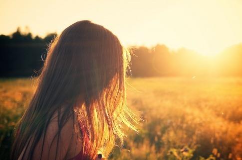 Eine Frau steht auf einem Feld im Sonnenschein