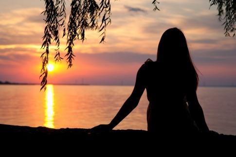 Eine Frau sitzt glücklich bei einem Sonnenuntergang