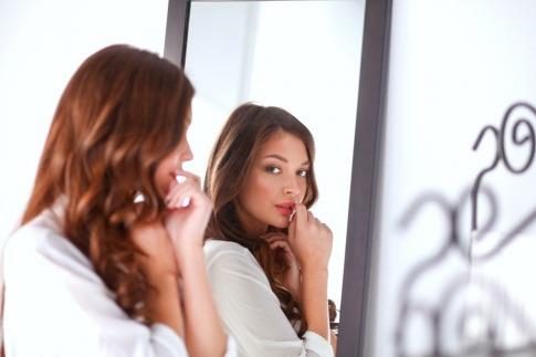 Eine Frau sieht selbstbewusst in den Spiegel